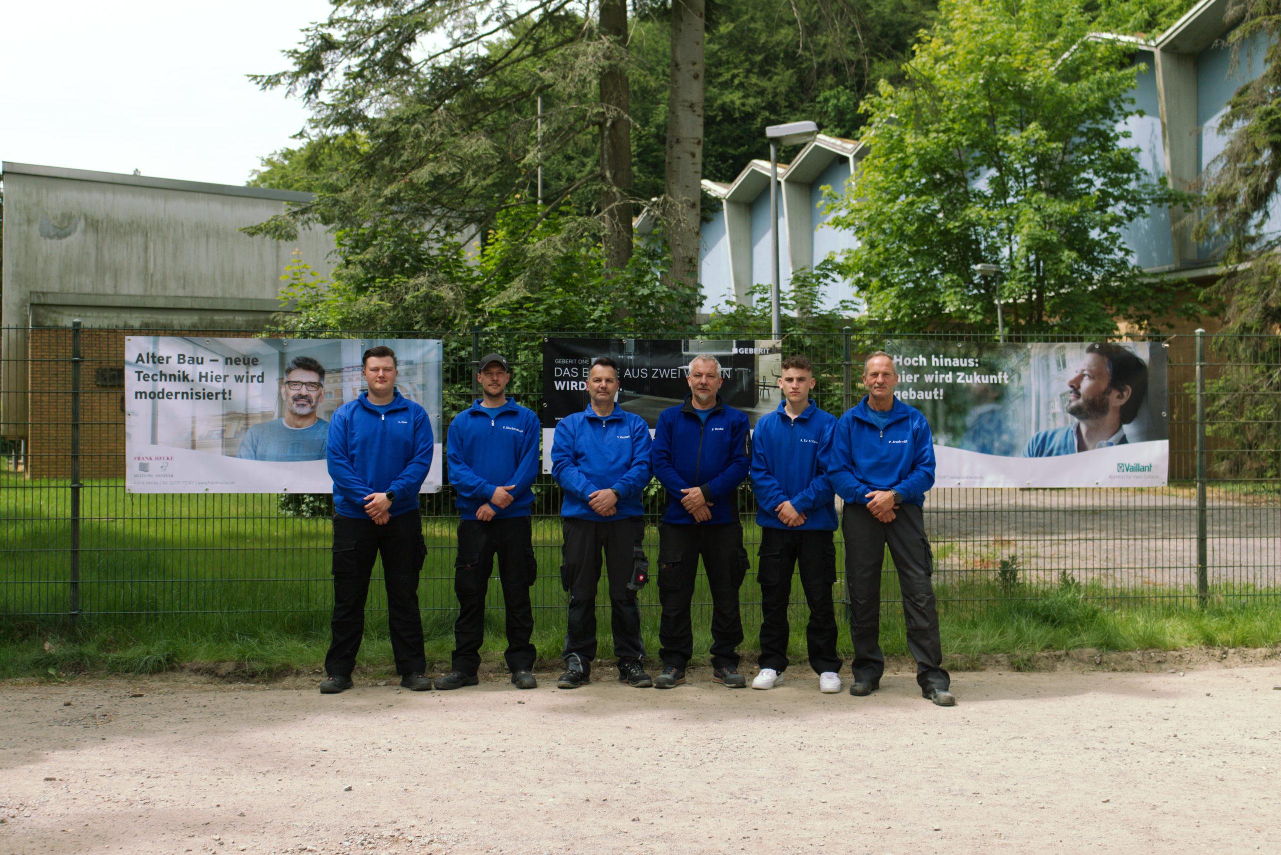 Unser gesamtes Team auf einem Bild mit unseren Werbeplakaten im Hintergrund