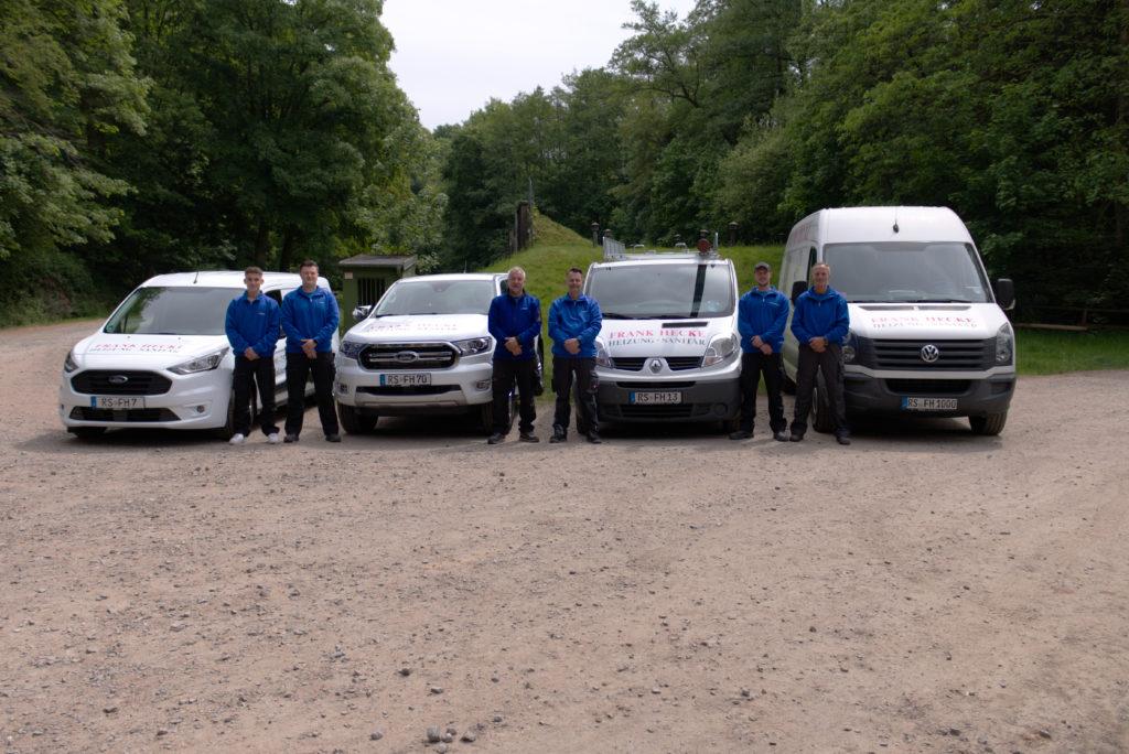 Unser Team posiert von den Firmenautos